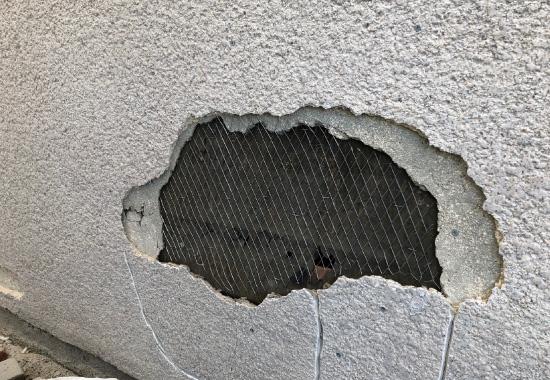 剥がれているモルタル外壁の写真